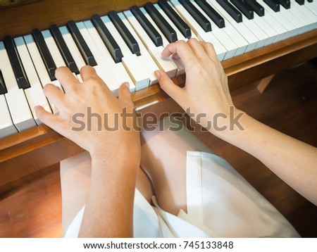 The blurred  hand of the pianist is pressing on piano keys .vintage tone,focus piano keys