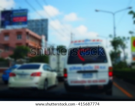 The blurry focus scene of emergency car on road through the car windscreen represent the car and transportation concept related idea. - stock photo
