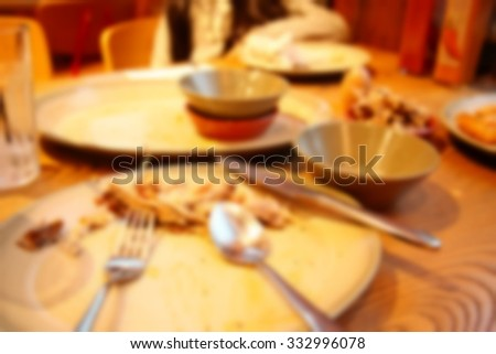 The blurry focus scene of leftover food and dish putting on dining table among restaurant scene represent the food restaurant concept related idea. - stock photo