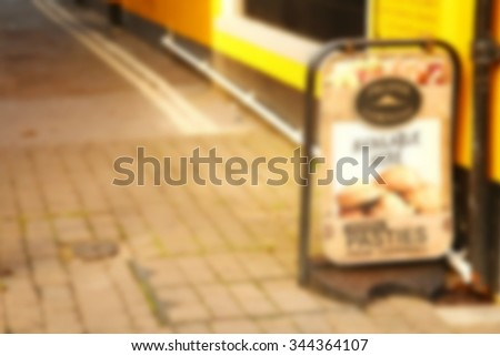 The blurry focus scene of restaurant advertising floor stand signage scene represent the signage and advertising concept related idea.