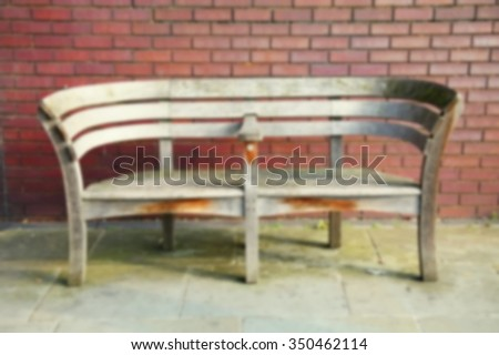 The blurry photo of public bench represent the outdoor and public equipment concept related idea.