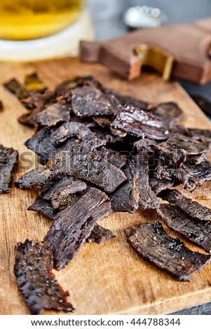 The board with homemade beef jerky - dried spiced meat, big glass of beer and bottle opener on back. Stone background. - stock photo