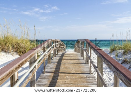 The boardwalk leads to the turquoise waters of the Gulf of Mexico at Park West on the western end of Pensacola Beach, Florida. - stock photo
