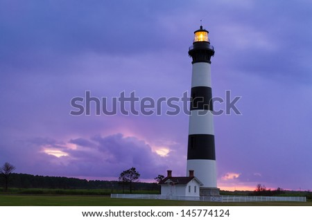 The Bodie Island Lighthouse, at Cape Hatteras National Seashore on North Carolina's Outer Banks, shines its beacon as the rising sun paints a cloudy sky with vivid colors. - stock photo
