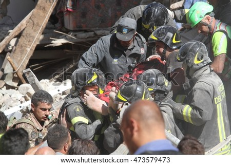 The body of a man is pulled from the rubble after the earthquake in Amatrice