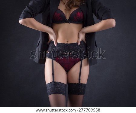 The body of a young woman in sexy lingerie on a dark background.