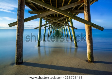The Bogue Inlet Pier at Emerald Isle, North Carolina is photographed here with a very long exposure. - stock photo