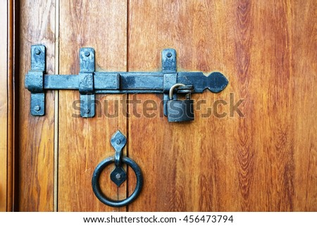 The bolt and lock on a wooden door