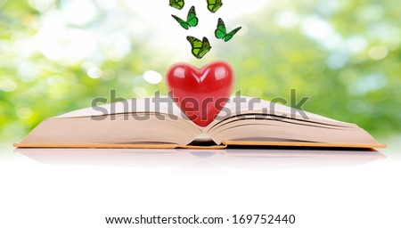 The book of love, a book open with a heart in the middle isolated on a green spring background