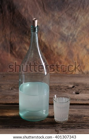 The bottle and glass of moonshine on the old wooden table