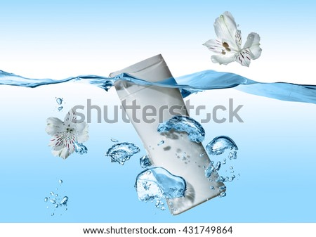 The bottle of cosmetic milk,  cream, tonic,  lotion in the blue water wave with splash and air bubbles under the water and with two white flowers near the bottle - stock photo
