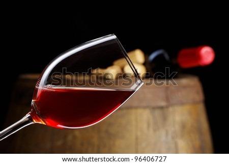 The bottle of red wine and glass and barrel - stock photo