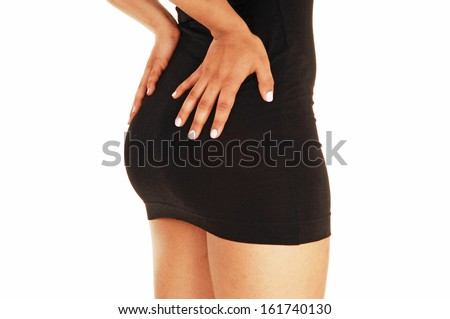 The bottom of a young woman in a short black dress standing in profile for white background.  - stock photo
