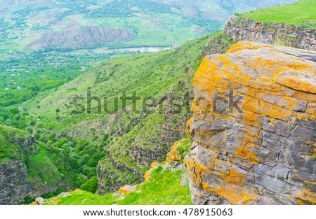 The boulders and rocks in mountain village of Saro covered with bright yellow and orange lichen, Georgia.