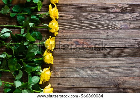 The bouquet of beautiful fresh yellow roses lies on a wooden table.  Card template by St. Valentine's Day or the international Women's Day.