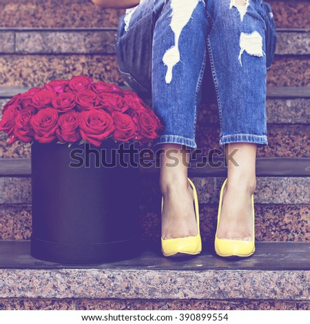 The bouquet of red roses and female legs in jeans and yellow shoes with heels. - stock photo