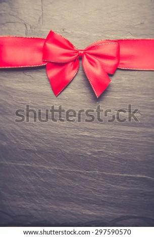 the bow of red ribbon on black background - stock photo