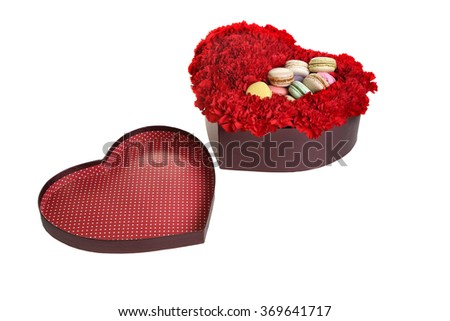 The box in the form of heart, is filled by flowers and cookies. Red carnations, white background.