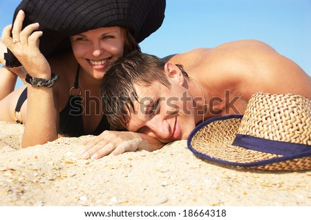 The boy and girl lay on sand (close-up)