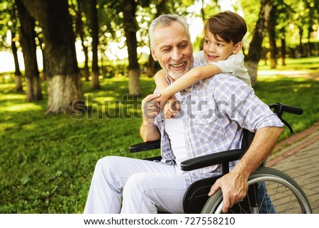The boy and his grandfather are walking in the park. The old man is sitting on a wheelchair. The boy stands behind the old man and hugs him. They are happy