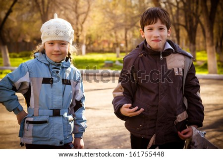 The boy and the girl of 9 years on walk in park in the autumn afternoon - stock photo