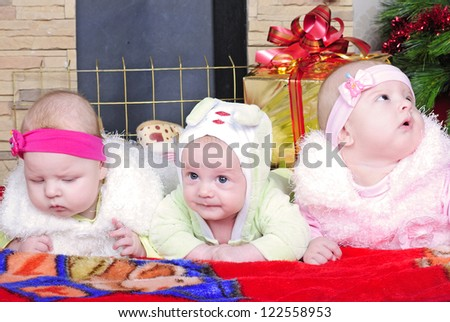 the boy and the Twins girls near a Christmas tree