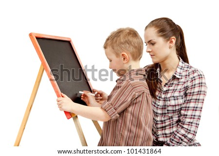 The boy begins to write on the blackboard. He wants to draw or write something. The young woman is  watching what he does. - stock photo