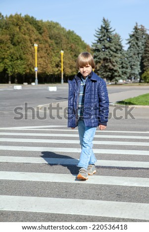 the boy crossed the road at a pedestrian crossing - stock photo