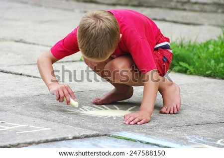 The boy draws on asphalt - stock photo
