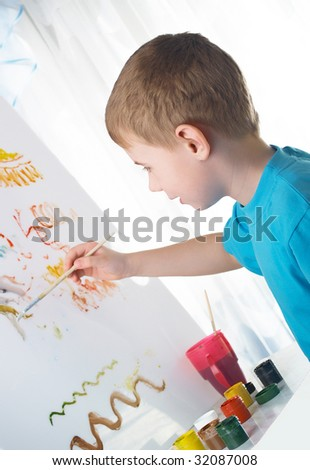 The boy draws with interest paints on a white cloth