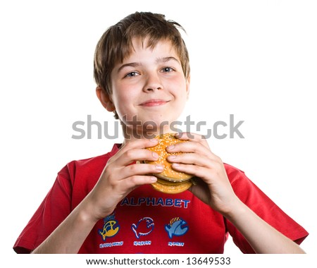 The boy eating a hamburger. Isolated on a white background. - stock photo
