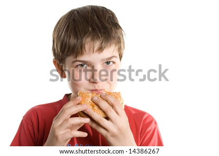 The boy eating a hamburger. Isolated on a white background.