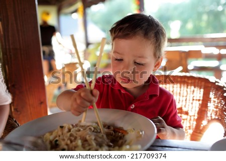 The boy eating noodles in an asian restaurant - stock photo
