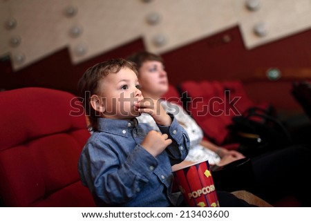 The boy eating popcorn in the cinema - stock photo