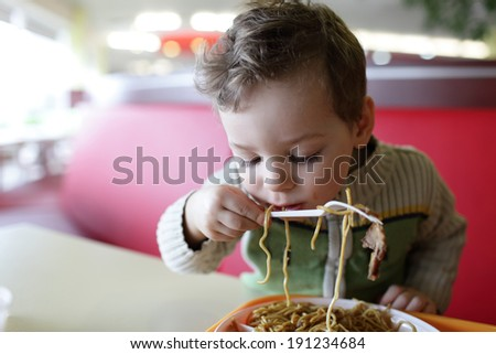 The boy eating spaghetti in the restaurant