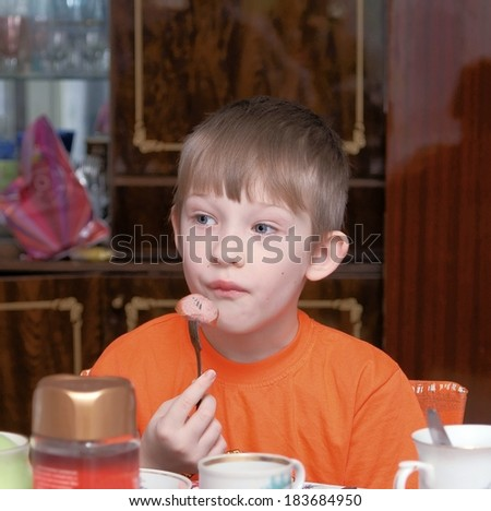 The boy eats sausage  - stock photo