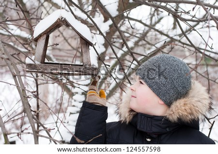 The boy feeds the birds in the feeder in winter - stock photo