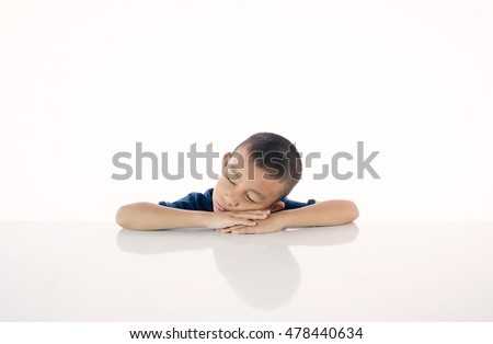 the boy fell asleep at the table on white background