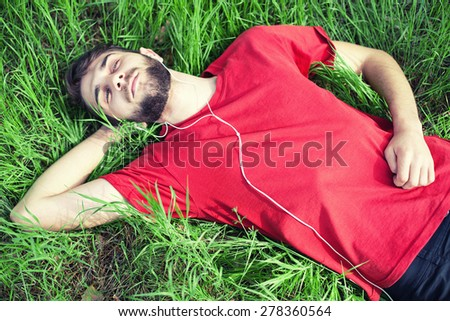 The boy in a green grass listens to music
