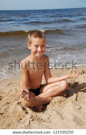 The boy in a lotus pose on the seaside