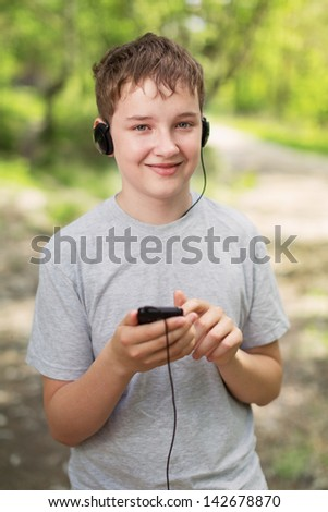 The boy in headphones listens to music in park