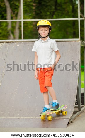 The boy in the cap standing on a skateboard