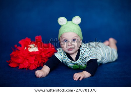 the boy in the hat frog lying on his tummy on a blue background - stock photo