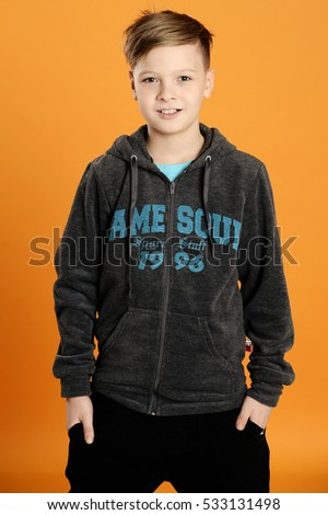 the boy in the jacket posing in a Studio on an orange background