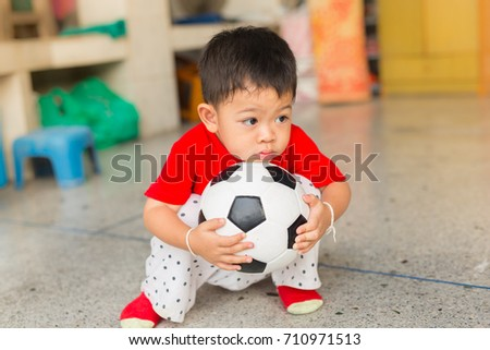 the boy is playing football alone inside of his house