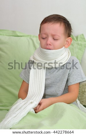 The boy is sick and crying. He sits on the bed