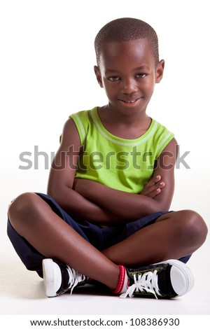 The boy is sitting with a big smile and also with crossed arms and legs.
