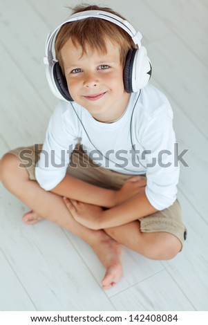 The boy is smiling  and listening to music - stock photo