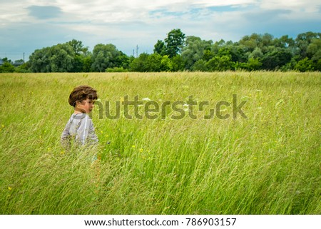 the boy is standing in the grass field