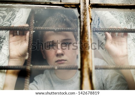The boy it is sad looks out of the window through a lattice